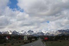 Visión panorámica con las casas rurales viejas de la meseta verde hermosa de la montaña de Zabljak a la montaña nevosa de Durmito fotografía de archivo