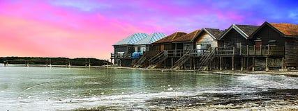 Visión panorámica, río hermoso, casas de madera viejas sobre el cielo colorido y nubes foto de archivo