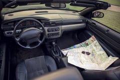 Visión por dentro de un coche en un tablero de instrumentos con un mapa y los vidrios de camino Tema del recorrido foto de archivo libre de regalías