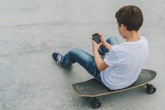 Visión posterior El adolescente se sienta en el monopatín, utiliza el smartphone, artilugio digital, juegos de ordenador de los j Fotos de archivo libres de regalías