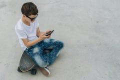 Visión posterior El adolescente se sienta en el monopatín, utiliza el smartphone, artilugio digital, juegos de ordenador de los j Fotos de archivo