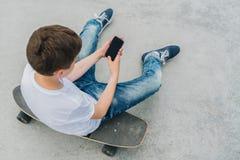 Visión posterior El adolescente se sienta en el monopatín, utiliza el smartphone, artilugio digital, juegos de ordenador de los j Fotografía de archivo