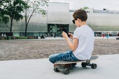 Visión posterior El adolescente se sienta en el monopatín, utiliza el smartphone, artilugio digital, juegos de ordenador de los j Imágenes de archivo libres de regalías
