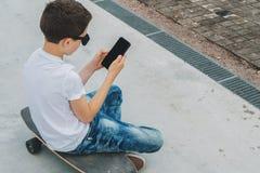 Visión posterior El adolescente se sienta en el monopatín, utiliza el smartphone, artilugio digital, juegos de ordenador de los j Foto de archivo