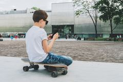 Visión posterior El adolescente se sienta en el monopatín, utiliza el smartphone, artilugio digital, juegos de ordenador de los j Foto de archivo libre de regalías
