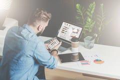 Visión posterior El hombre de negocios barbudo joven en camisa se sienta en oficina en la tabla y utiliza smartphone con las cart Fotografía de archivo