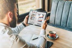 Visión posterior El hombre de negocios barbudo joven en la camisa blanca se está sentando en la tabla, usando la tableta con los  Fotos de archivo libres de regalías