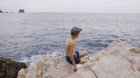 Visión posterior El niño pequeño en pantalones cortos con el casquillo se sienta en la playa pedregosa en la bahía rocosa en un d almacen de video