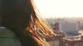 Visión posterior El viento sopla a mujeres jovenes hermosas largas del pelo oscuro Muchacha que se coloca en el tejado en la pues almacen de video
