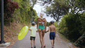 Visión posterior La mamá y dos hijos están caminando en el parque por el mar Una mujer joven en un traje de baño y un sombrero gr almacen de video