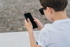Visión posterior Primer del smartphone en manos del muchacho El adolescente sienta al aire libre, utiliza el artilugio, Internet  Fotos de archivo