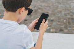 Visión posterior Primer del smartphone en manos del muchacho El adolescente sienta al aire libre, utiliza el artilugio, Internet  Fotografía de archivo libre de regalías