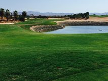 Visión sobre el agujero del golf en España con peligro del agua en frente foto de archivo libre de regalías
