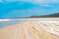 Visión sobre la playa defocused con las pistas del neumático fotografía de archivo