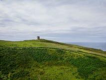 Visión sobre las colinas y un edificio viejo cerca del mar en Donegal Fotos de archivo