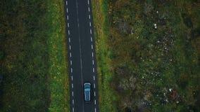 Visión superior aérea, abejón que enfoca adentro en el coche negro que se mueve a lo largo del camino de la carretera a lo largo  almacen de video