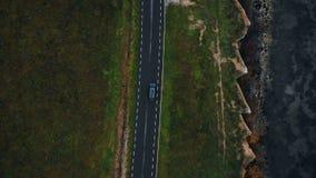 Visión superior aérea que sigue el tiro del coche negro que se mueve a lo largo del camino épico de la carretera a lo largo de la almacen de metraje de vídeo