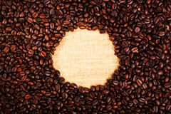 Visión superior con el espacio de la copia, granos de café asados con el fondo de la arpillera Fotos de archivo