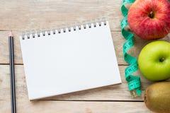 Visión superior con la cinta métrica, la manzana, el lápiz y el cuaderno en el fondo de madera de la tabla fotos de archivo