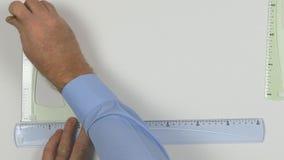 Visión superior con las manos del ingeniero que comienzan a dibujar un proyecto técnico almacen de metraje de vídeo