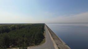 Visión superior desde el dron del bosque verde asombroso a la izquierda, del lago azul a la derecha, y del camino recto largo en  metrajes