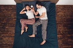 Visión superior El hombre hermoso adulto con el despertador despertó a la mujer joven que mentía en cama Fotos de archivo