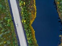 Visión superior en la conducción de automóviles en el camino de tierra en swampland con la ventana del lago Fotografía de archivo libre de regalías