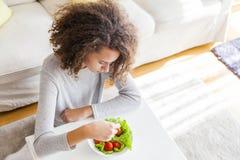 Visión superior en la muchacha adolescente del pelo rizado que come la ensalada Imagenes de archivo