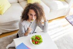 Visión superior en la muchacha adolescente del pelo rizado que come la ensalada Imagen de archivo