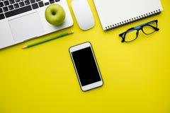 Visión superior, endecha plana de la tabla amarilla moderna del escritorio de oficina con lapto Imagen de archivo