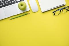 Visión superior, endecha plana de la tabla amarilla moderna del escritorio de oficina con lapto Imagenes de archivo