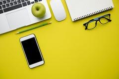 Visión superior, endecha plana de la tabla amarilla moderna del escritorio de oficina con lapto Foto de archivo