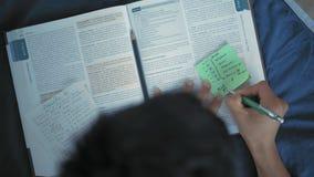 Visión superior, estudiante indio que toma notas del libro en la etiqueta engomada, mintiendo en la cama metrajes