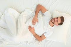 Visión superior hombre feliz que miente en el sofá Imagen de archivo