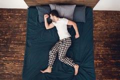 Visión superior Hombre hermoso en funcionamientos de los pijamas en sueño Sirva los sueños que él está funcionando con lejos algu imagen de archivo libre de regalías