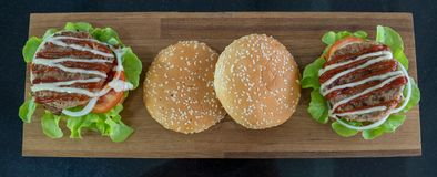 Visión superior, ingredientes de las hamburguesas colocadas en una tabla de cortar de madera fotografía de archivo libre de regalías