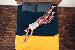 Visión superior La chica joven con el tubo respirador en boca imita el buceo con escafandra, mintiendo en cama imagen de archivo