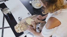 Visión superior La niña y su madre que amasan la pasta para hacen las galletas juntas en la cocina en casa Madre y almacen de metraje de vídeo