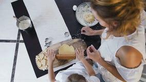 Visión superior La niña y su madre que amasan la pasta para hacen las galletas juntas en la cocina en casa Madre y metrajes