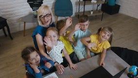 Visión superior Los estudiantes con el profesor se están sentando en la tabla en la clase geográfica, consideran para arriba la c almacen de metraje de vídeo