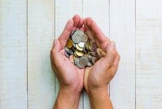 Visión superior muchas monedas en manos Imágenes de archivo libres de regalías