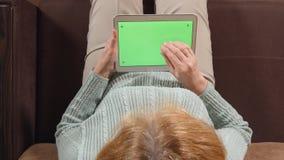 VISIÓN SUPERIOR: Mujer envejecida con una pantalla del verde de la tableta en un sofá - ascendente cercano almacen de metraje de vídeo
