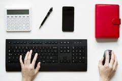 Visión superior, mujer que se sienta en el escritorio y que trabaja en su PC, su tabla Imagenes de archivo
