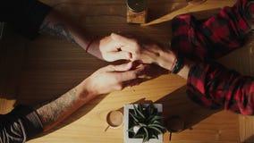 Visión superior Pares cariñosos que llevan a cabo las manos en un café almacen de video