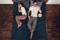 Visión superior Película de observación del hombre joven y palomitas de la consumición en cama mientras que está durmiendo la muj foto de archivo libre de regalías