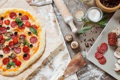 Visión superior que cocina la pizza con los ingredientes, los tomates, el salami y las setas en el tablero de la mesa de madera fotos de archivo