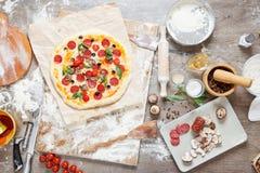Visión superior que cocina la pizza con los ingredientes, los tomates, el salami y las setas en el tablero de la mesa de madera foto de archivo