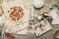 Visión superior que cocina la pizza con los ingredientes, los tomates, el salami y las setas en el tablero de la mesa de madera fotografía de archivo libre de regalías