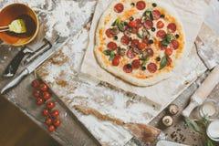 Visión superior que cocina la pizza con los ingredientes, los tomates, el salami y las setas en el tablero de la mesa de madera foto de archivo libre de regalías
