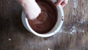 Visión superior que revuelve la pasta con una cuchara en un cuenco, vídeo acelerado de la galleta del chocolate metrajes